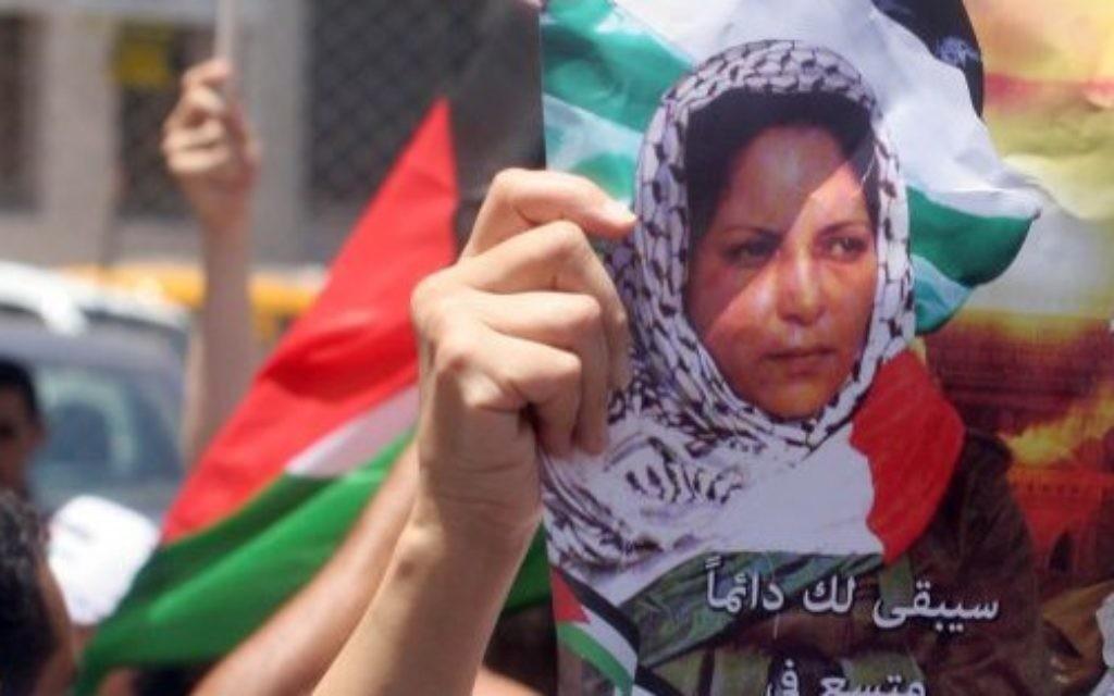 Des Palestiniens avec des affiches et des T-shirts représentant Dalal Mughrabi, une terroriste du Fatah responsable du massacre de la route côtière en 1978, qui a tué 38 Israéliens dont 13 enfants, pendant une manifestation à Ramallah, le 16 juillet 2008. (Crédit : Issam Rimawi/Flash90)