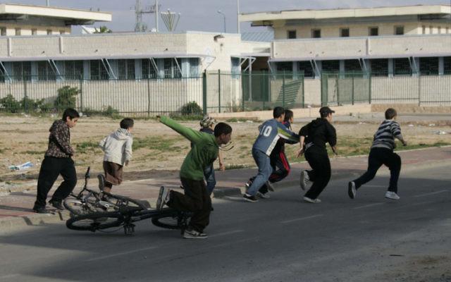 Des enfants israéliens se précipitent vers un abri pendant une alarme à la roquette provenant de la bande de Gaza, le 8 janvier 2009. (Crédit : Anna Kaplan/Flash90)