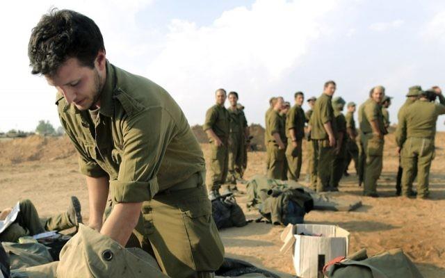 Un soldat réserviste de l'armée israélienne en train d'emballer son sac avant de quitter une zone de déploiement près de la frontière de Gaza, en novembre 2012 (Crédit : Tsafrir Abayov / Flash90)