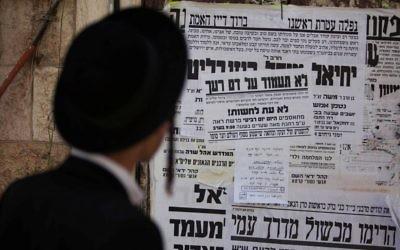 Un Juif ultra-orthodoxe lit une affiche appelant à la libération d'un membre de la secte juive anti-sioniste Neturei Karta, le 1er août 2013. Illustration. (Crédit : Yonatan Sindel/Flash90)