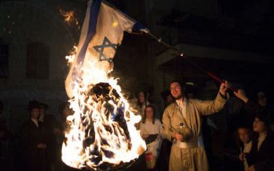 Un membre de la secte anti-sioniste Neturei Karta brûle un drapeau israélien pendant la fête de Lag BaOmer, dans le quartier ultra-orthodoxe de Mea Shearim, à Jérusalem, en mai 2014. (Crédit : Yonatan Sindel/Flash90)