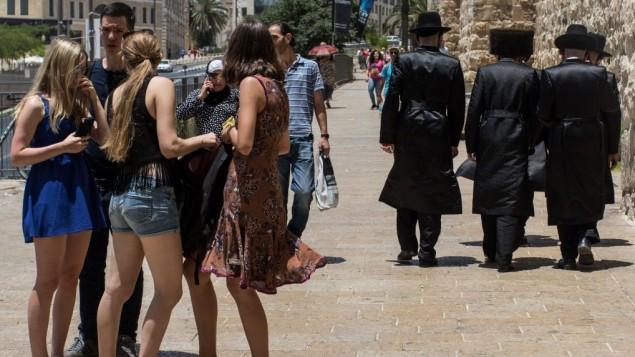 Un groupe de femmes croise un groupe d'hommes juifs orthodoxes à proximité de la porte de Jaffa dans la vieille Ville de Jérusalem, le 13 juin 2016 (Crédit : Zack Wajsgras/Flash90)