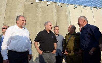 Le Premier ministre Benjamin Netanyahu et le ministre de la Défense Avigdor Liberman, avec le député Avi Dichter et le chef d'Etat-major Gadi Eizenkot, devant une nouvelle section de la barrière de sécurité entre Israël et la Cisjordanie, près de Tarqumiyah, le 20 juillet 2016. (Crédit : Haim Zach/GPO)