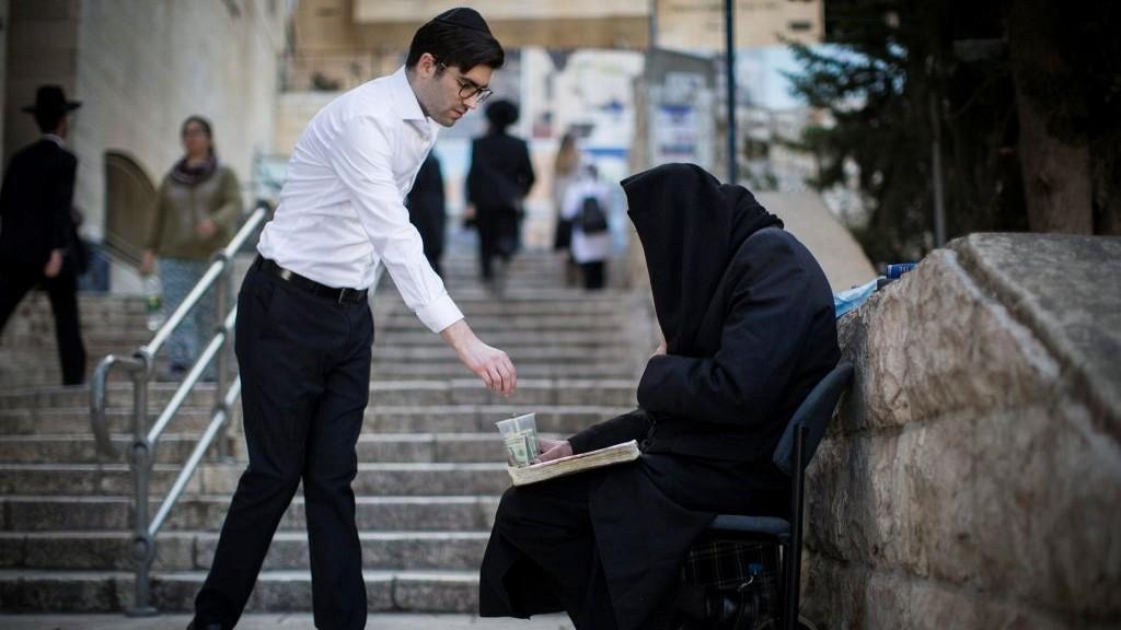 Un ultra-orthodoxe donne de la monnaie à une mendiante le long de l'escalier qui mène du quartier juif de la Vieille ville à Jérusalem au mur Occidental, le 26 février 2017. (crédit : Hadas Parush/Flash90)