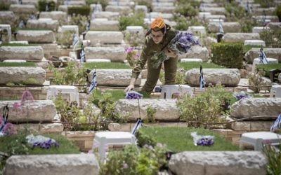 Avant Yom HaZikaron, une soldate place des fleurs sur les tombes des soldats morts au combat, au cimetière militaire du mont Herzl, à Jérusalem, le 30 avril 2017. (Crédit: Yonatan Sindel/Flash90)