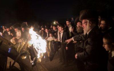 Des Juifs ultra-orthodoxes devant un immense feu de joie pendant la célébration de Lag BaOmer, dans le quartier de Mea Shearim, à Jérusalem, le 13 mai 2017. (Crédit : Flash90)