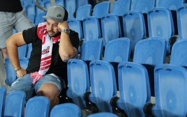 Un fan dépité regarde l'Hapoel Tel Aviv perdre ;  l'équipe chute en deuxième division, le 13 mai 22017. (Crédit : Roy Alima/Flash90)
