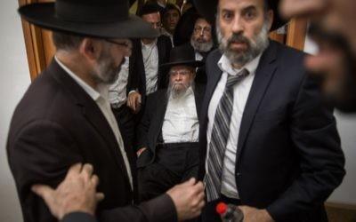 L'ancien grand rabbin séfarade Eliyahu Bakshi Doron, assis au centre, à son arrivée devant la cour du district de Jérusalem, entourés de ses soutiens qui tentent de cacher son visage, le 15 mai 2017. (Crédit : Hadas Parush/Flash90)
