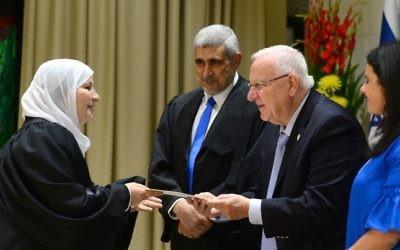 La ministre de la Justice Ayelet Shaked, le président Reuven Rivlin, et le président de la cour d'appel islamique, le qadi Abed Alhakim Samara, donnent son certificat à la toute première femme nommée au poste de juge islamique , Hana Mansour Khatib, à la résidence du président le 15 mai 2017 (Crédit :  Mark Neyman/GPO)