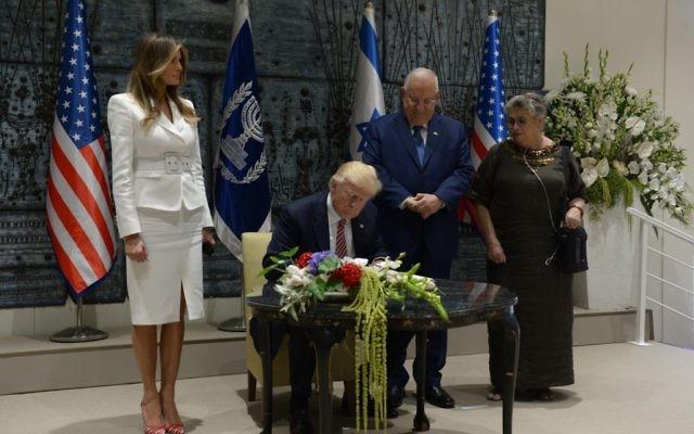 Le président Reuven Rivlin derrière son homologue américain Donald Trump, qui signe le livre d'or, avec leurs épouses Melania Trump et Nechama Rivlin, à la résidence présidentielle de Jérusalem, le 22 mai 2017. (Crédit : Haim Zach/GPO)