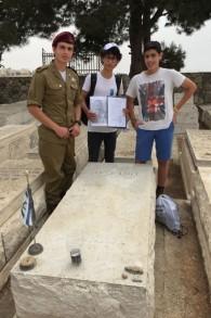 Les étudiants Moshe Abulafia (au milieu) et Yotam Marsh avec un soldat, devant la tombe d'Hans Beit,un officier de l'immigration allemand, enterré au Mpnt des Oliviers. (Crédit : Jessica Steinberg/Times of Israel)