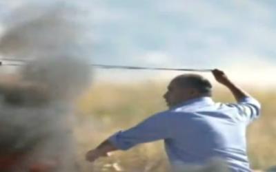 Jamal Hawil, député de l'Autorité palestinienne, jette des pierres contre des soldats israéliens pendant des affrontements près du carrefour Beit El, en Cisjordanie, le 13 mai 2017. (Crédit : capture d'écran Deuxième chaîne)