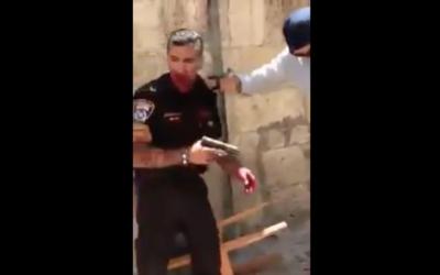 Une image de la séquence montrant un agent de police après qu'il a été poignardé par un agresseur, le samedi 13 mai, dans la Vieille ville de Jérusalem. La police a indiqué que l'agent a ensuite tiré sur l'attaquant, un Jordanien, qui est mort de ses blessures. Le policier a été hospitalité avec des blessures modérées (Capture d'écran : : Quds News Network/Twitter)