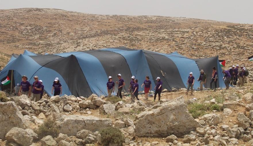 Un groupe de militants d'Israël, des territoires palestiniens et du monde entier au 'camp de la liberté de Sumud' dans les collines du sud dr Hebron, le vendredi 19 mai 2017 (Crédit : Gili Getz)