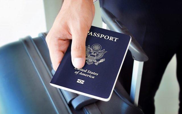 Homme tenant un passeport américain (Crédit : Shutterstock)