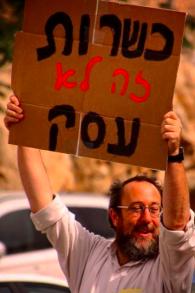 """Le rabbin Aaron Leibowitz avec un panneau """"la casheroute n'est pas un commerce"""". (Crédit : autorisation de Yerushalmim)"""