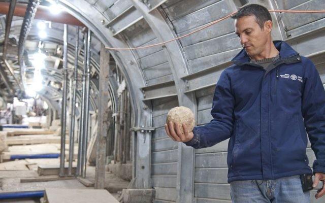Nahshon Szanton tenant une pierre d'arbalète qui aurait été catapultée durant le siège de Jérusalem,  dans une rue antique où des fouilles sont actuellement menées (Crédit : Shai Halevy/Autorisation : Autorité des antiquités israéliennes)