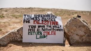 """Bannière installée par des militants devant le """"camp de la liberté Sumud"""" fondé dans les collines du sud de Hébron en solidarité avec les Palestiniens, le 19 mai 2017. l est écrit : """"Juif américain, je soutiens la justice pour la Palestine. Abattez le mur, libérez tous les prisonniers politiques, rendez les terres volées"""". (Crédit : Rami Ben Ari)"""