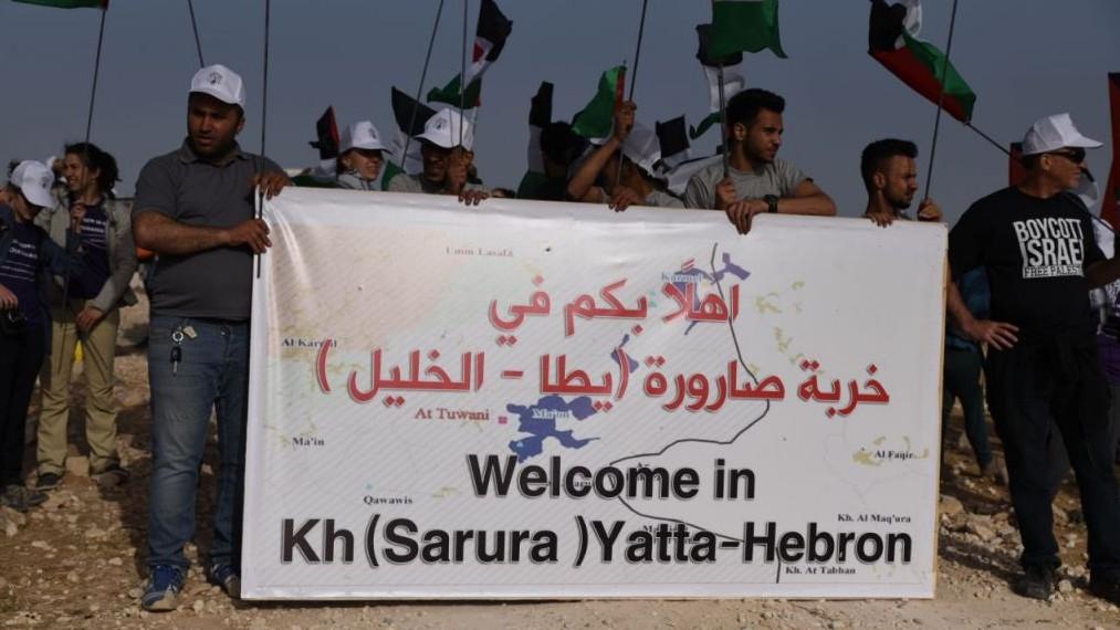 """Des militants derrière la bannière placée à l'entrée du """"camp de la liberté Sumud"""" dans les collines du sud de Hébron, en mai 2017. (Crédit : Rami Ben-Ari)"""