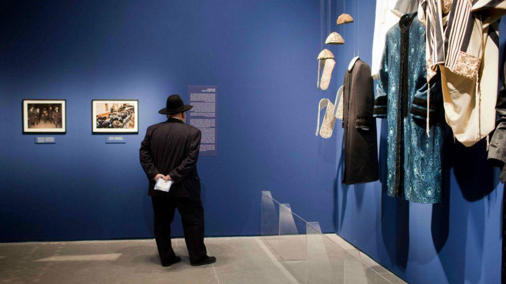 """Des visiteurs contemplent l'exposition au musée d'Israël : """"A World Apart Next Door: Glimpses into the life of Hasidic Jews"""" à Jérusalem, le 20 juin 2012. L'exposition met en lumière différents aspects de la culture des juifs hassidiques. (Crédit : Yonathan Sindel/Flash90)"""