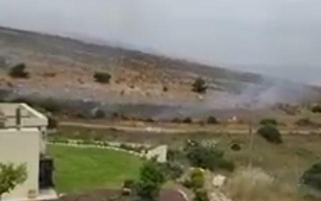 De la fumée émane d'un champ incendié par les sympathisants du Hezbollah près de la ville frontalière de Metoula, le 25 mai 2017. (Crédit : capture d'écran)