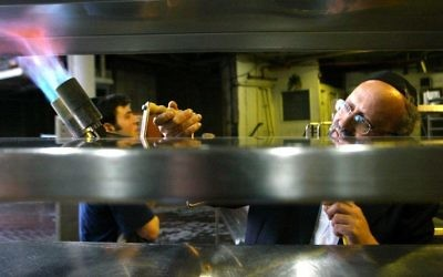 Le rabbin chargé de la casheroute au Sheraton Crown Plaza utilise un chalumeau pour eliminer toute trace de levain dans les cuisines de l'hôtels, avant Pessah, le  2 avril 2006. (le Sheraton n'a pas été incus dans le reportage de la Dixième chaîne). (Crédit : Olivier Fitoussi/Flash90)