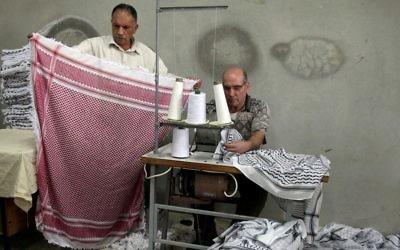 Des Palestiniens travaillent dans une fabrique de Keffieh, à Hébron, en Cisjordanie, le 14 octobre 2010. (Crédit : Najeh Hashlamoun/Flash90)