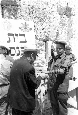 Un soldat se fait poser des tefillins au mur Occidental, le 17 juin 1967. (Crédit : collection de Dan Hadani/Bibliothèque nationale d'Israël)