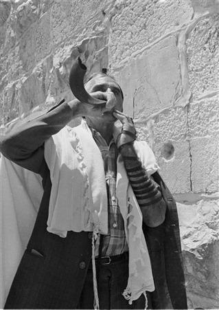 Un homme souffle dans un shofar au mur Occidental, le 22 juin 1967. (Crédit : collection de Dan Hadani/Bibliothèque nationale d'Israël)