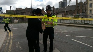 Le rabbin Shneur Cohen distribue des boissons chaudes et des viennoiseries à la police qui travaille sur les lieux de l'attentat qui a frappé Manchester, au Royaume-Uni, le 23 mai 2017. (Crédit : Chabad of Manchester City Center)