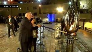 Le président Reuven Rivlin allume la flamme du souvenir avec la veuve d'un soldat israélien mort au combat, Hagi Ben Ari, pendant la cérémonie officielle de Yom HaZikaron au mur Occidental, à Jérusalem, le 30 avril 2017. (Crédit : capture d'écran Deuxième chaîne)