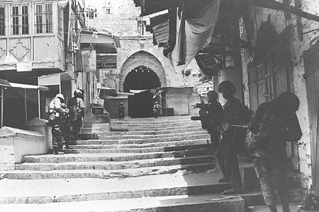 Une unité de parachutistes israéliens traverse une ruelle de la Vieille Ville de Jérusalem durant la guerre des Six Jours, en juin 1967. (Crédit : GPO)
