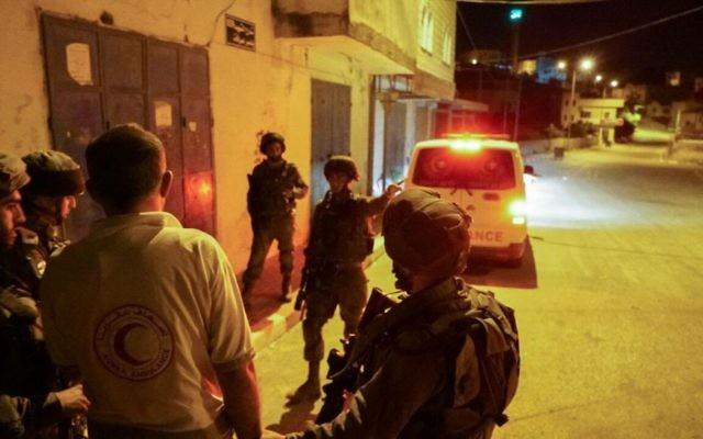 Des soldats arrêtent un conducteur d'ambulance, qui a empêché un véhicule israélien dans le nord de la Cisjordanie le 19 mai 2017. L'ambulance a bloqué la fuite d'un Israélien qui a été attaqué par une foule lors d'une manifestation dans le village de Hawara, en dehors de Naplouse. (Crédit : Unité des porte-paroles de l'armée israélienne)