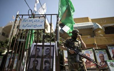Un membre des Brigades Ezzedine al-Qassam, l'a branche armée du groupe terroriste du Hamas, à côté de fausses prisons lors d'un rassemblement marquant la Journée des prisonniers palestiniens dans la ville de Gaza, le 17 avril 2016. (Crédit : Mahmud Hams/AFP)