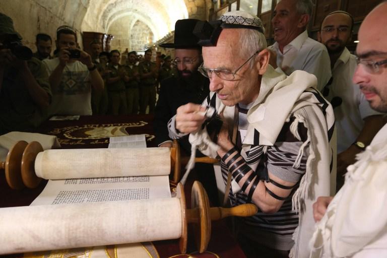 Des survivants juifs de l'Holocauste portent le tefilin, ou les phylactères, et le châle de prière pendant qu'ils lisent les rouleaux de la Torah lors de leur cérémonie de bar mitzvah, normalement faite à l'âge de 13 ans, le 2 mai 2016, au mur Occidental de la Vieille Ville de Jérusalem . (Crédit : AFP Photo / Menahem Kahana)