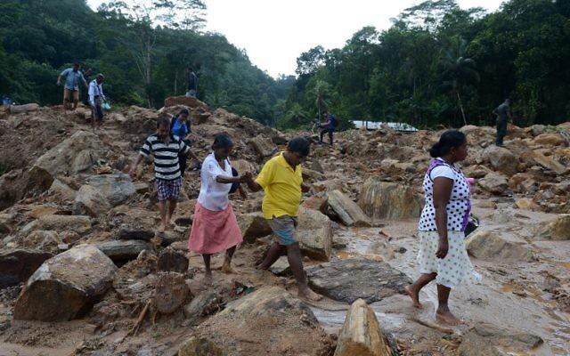 Les villageois sri lankais traversent un site touché par un glissement de terrain alors que les secouristes et les villageois cherchent des survivants dans le village d'Athweltota à Kalutara le 28 mai 2017. (Crédit : AFP PHOTO / LAKRUWAN WANNIARACHCHI)