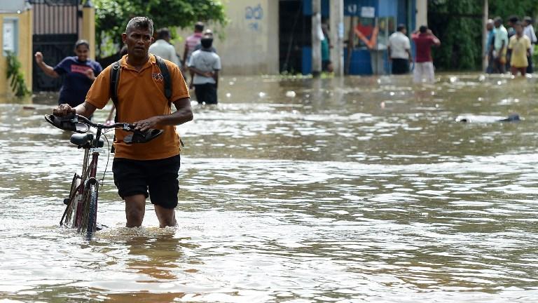 Les résidents sri lankais traversent une zone inondée  dans le village de Dodangoda à Kalutara le 28 mai 2017. (Crédit : AFP PHOTO / Lakruwan WANNIARACHCHI)