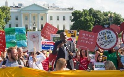 Des manifestants brandissent des pancartes durant une manifestation devant la Maison Blanche à Washington, le 1er juin 2017, s'opposant à la décision du président  Donald Trump de se retirer des accords de Paris sur le climat (Crédit : PAUL J. RICHARDS/AFP PHOTO /)