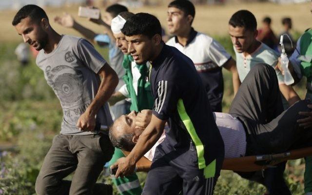 Des Palestiniens transportent un homme blessé pendant des affrontements contre l'armée israélienne près de la frontière entre la bande de Gaza et Israël, à l'est du camp de réfugiés de Jabalia, le 5 juin 2017. (Crédit : Mahmud Hams/AFP)