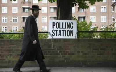 Un Juif ultra-orthodoxe passe devant un bureau de vote dans le nord-est de Londres le 8 juin 2017 (Crédit :  Daniel Leal-Olivas/AFP)