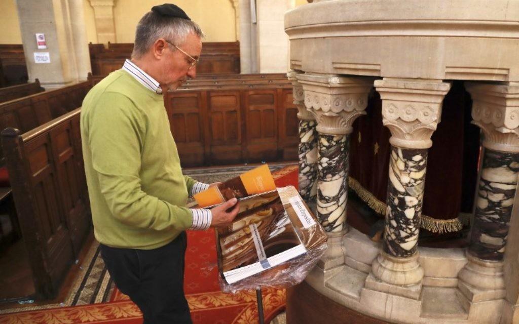Jacques Canet, président de la Grande Synagogue de Paris (Synagogue de la Victoire), lisant un livre consacré au 150e anniversaire de la synagogue, à Paris le 8 juin 2017 (Crédit : AFP PHOTO / JACQUES DEMARTHON