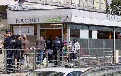 Des policiers enquêtent sur l'explosion d'une bombe dans un supermarché casher de Sarcelles, après que deux hommes masqués on lancé une grenade à l'intérieur du magasin en plein jour, le 19 septembre 2012. (Crédit : Joël Saget/AFP)