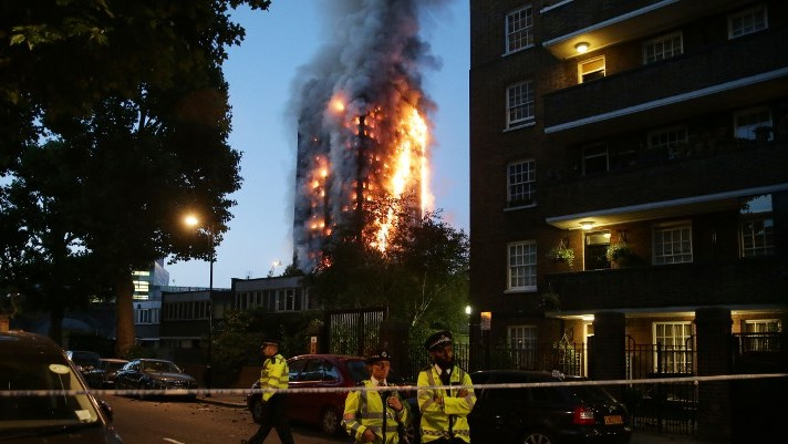 Des policiers gardent un cordon de sécurité alors qu'un immense incendie ravage la Grenfell Tower à l'ouest de Londres, le 14 juin 2017 (Crédit : Daniel Leal-Olivas/AFP Photo)