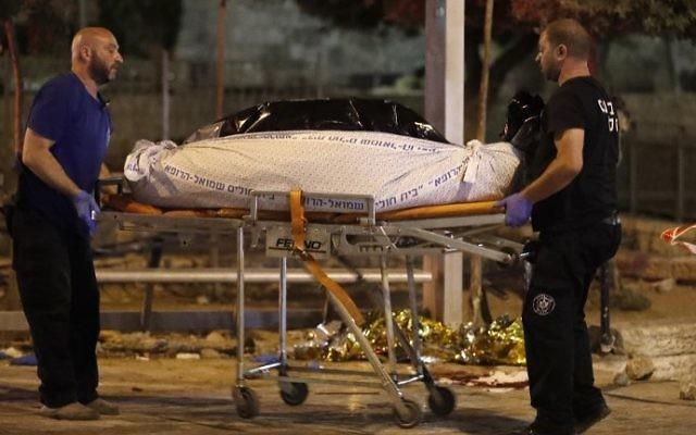 La police scientifique évacue les corps des terroristes palestiniens de la Vieille Ville de Jérusalem, le 16 juin 2017. (Crédit : Ahmad Gharabli/AFP)