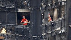 Les membres des services d'urgence travaillent dans les étages des ruines de la Grenfell Tower, ravagée par les flammes le 14 juin, à Kensington dans l'ouest de Londres, le 17 juin 2017 ( Crédit : Tolga AKMEN/AFP PHOTO)