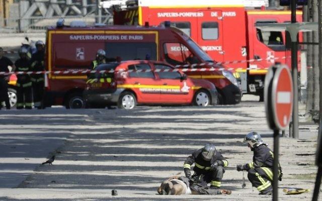 Secouristes penchés sur le corps d'un terroriste présumé dans une zone bouclée des Champs-Elysées, à Paris, le 19 juin 2017. (Crédit : Thomas Samson/AFP)