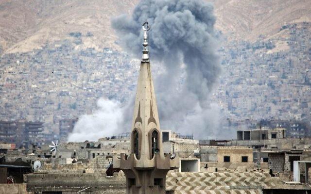 Fumée visible après une frappe aérienne dans les quartiers rebelles de Jobar, à l'est de Damas, en Syrie, le 21 juin 2017. (Crédit : Amer Almohibany/AFP)