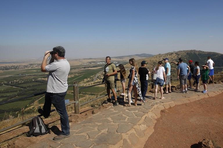 Des touristes israéliens observent la Syrie depuis le mont Bental, sur le plateau israélien du Golan, le 24 juin 2017. (Crédit : Jalaa Marey/AFP)