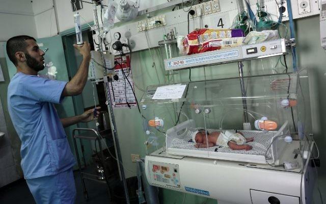 Un infirmier palestinien prenant soin d'un nouveau-né à l'unité de néonatalogie à l'hôpital des Emirats arabes unis à Rafah, dans le sud de la bande de Gaza, le 27 juin 2017. (Crédit : Said Khatib/AFP)