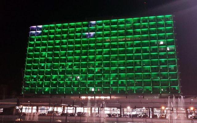 La mairie de Tel Aviv illuminée de vert pour protester contre la décision américaine de se retirer des accords de Paris sur le climat, le 4 juin 2017. (Crédit : Ron Huldai via Facebook)